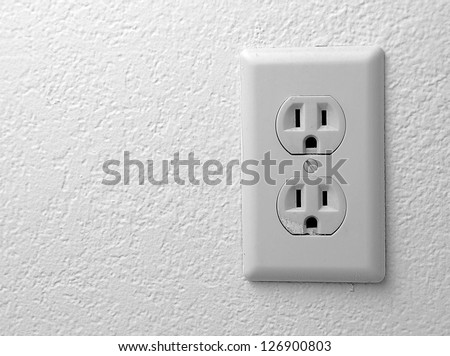 Electric outlet on the wall covered with wallpaper. - stock photo