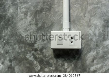 Electric plug and switch on grey wall, background - stock photo