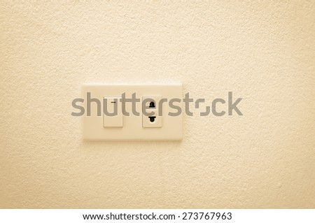 electric plug and switch on wall , sepia  - stock photo