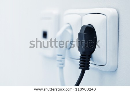 electric plug in a socket closeup. Small shallow DOF - stock photo
