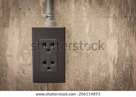 Electric plug on grunge cement wall background - stock photo