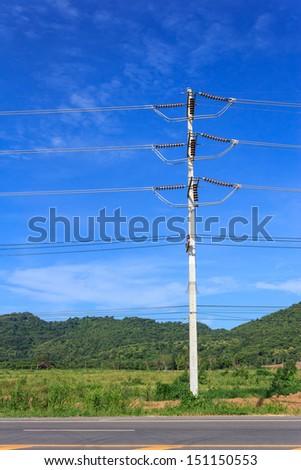 Electric pole on a blue sky background - stock photo