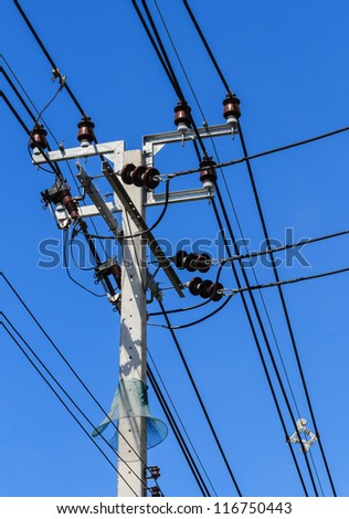 Electric Pole with Power Lines against Bright Blue Sky with Snake Protector - stock photo