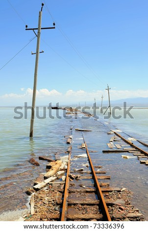 electric poles and rail in water during a spring floods - stock photo