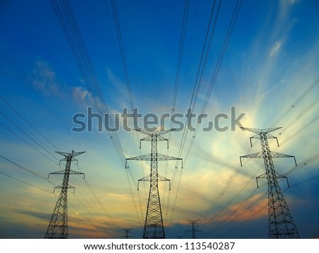 Electric post in a field and blue sky - stock photo