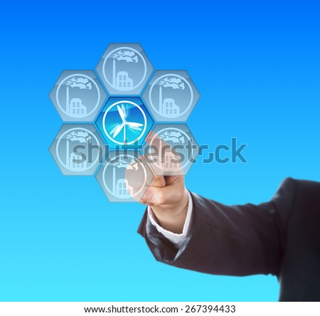 Electric power generation through wind energy. Arm of a business manager activating a wind turbine symbol on a touch screen interface. Metaphor for energy transition, the so called Energiewende. - stock photo