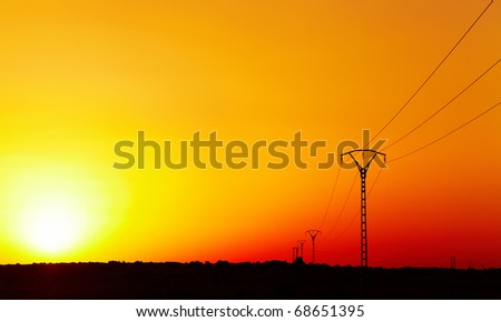 Electric power line in Sahara Desert against colorful sky at sunset - stock photo