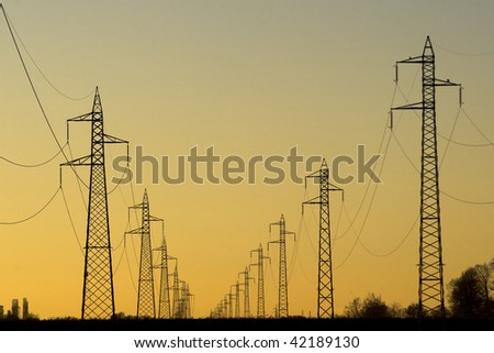 Electric power line, sunset in background - stock photo