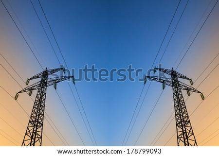 Electric power lines and pylons against blue and yellow sky - stock photo