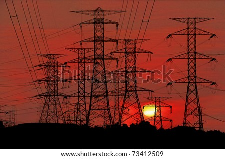 Electric power pylon congested on a hill against a surreal bloody red sunset. - stock photo