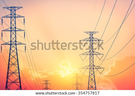 Electric power transmission against sky at sunset - stock photo