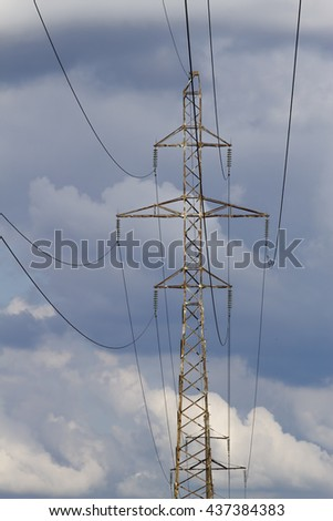 Electric power transmission lines and electricity pylon against blue sky. Low angle view - stock photo