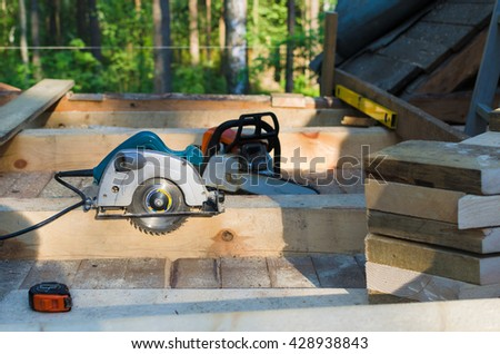 Electric saw in building area. tools in wooden house. building ecological house - stock photo
