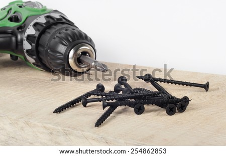 electric screwdriver screws on the wooden background - stock photo