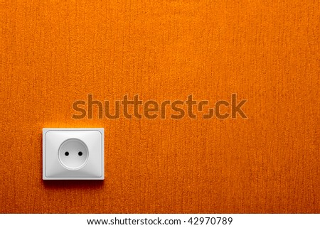 Electric socket in a orange wall in the corner - stock photo