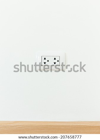 Electric socket on white wall. - stock photo