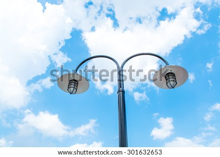 Electric Street lamp against blue sky - stock photo
