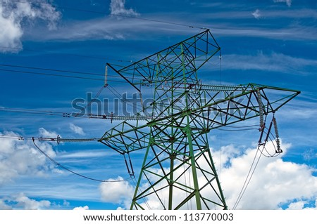 Electric support with wires and insulators against the cloudy sky - stock photo