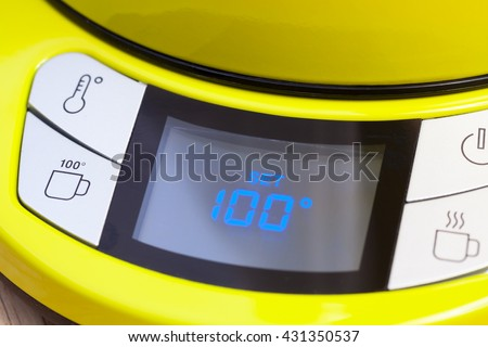 Electric tea kettle with digital thermostat control panel set to temperature of 100 degrees Celsius for brew black tea - stock photo
