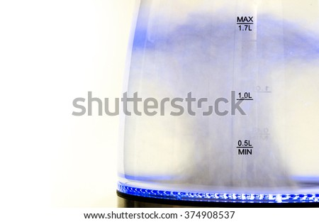 electric teapot kettle with a boiling water inside and color backlight isolated in white background / glass electric kettle with boiling water, isolated on white closeup - stock photo