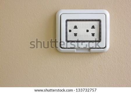 Electric wall plug at a orange wall - stock photo