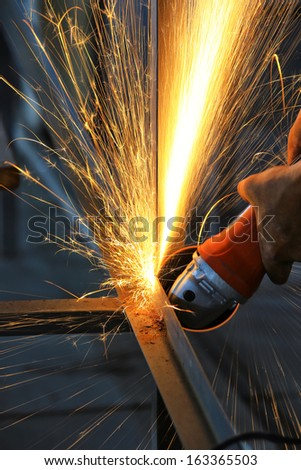 Electric wheel cutting on steel structure in factory  - stock photo