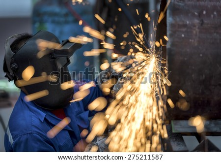 Electric wheel grinding on steel pipe in factory - stock photo