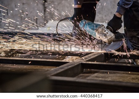 Electric wheel grinding on steel structure in factory. - stock photo