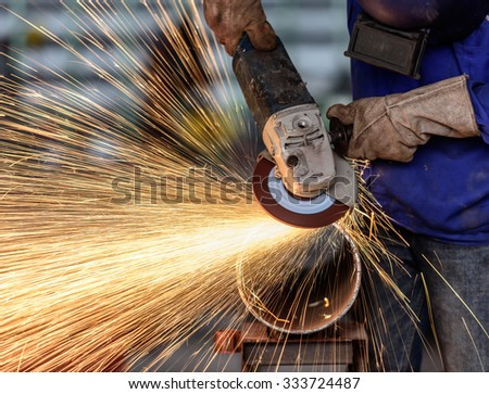 Electric wheel grinding on steel structure in factory (Low speed shutter) - stock photo