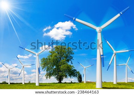Electric Wind Generators in Countryside. Seven wind turbines in countryside with tree, blue sky, clouds and sun rays - stock photo