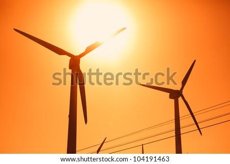 Electric wind turbines farm silhouettes on sun background - stock photo