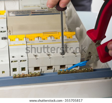 electrical appliance repairs. electrician fixing cable in domestic electrical plastic box - stock photo