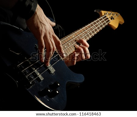 electrical bass-guitar in male hands, black background - stock photo