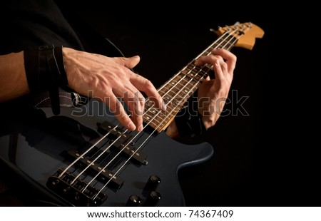 electrical bass guitar in male hands, black background - stock photo