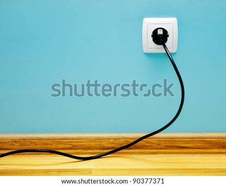 Electrical cable into the socket. Home shot. - stock photo
