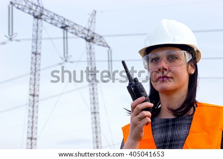Electrical distribution engineer talking  on a walkie- talkie ; Supervising female engineer for electrification using walkie- talkies near the transmission line - stock photo