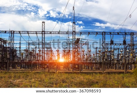 Electrical distribution station, transformers, high-voltage lines in sunrise with clouds - stock photo