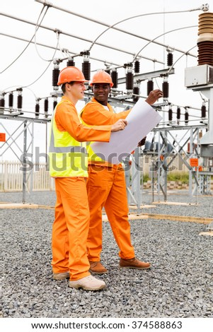 electrical engineer holding blueprint in electric substation - stock photo