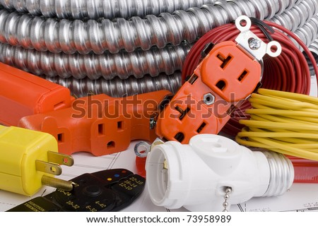Electrical equipment laying on a series of electrical plans. - stock photo