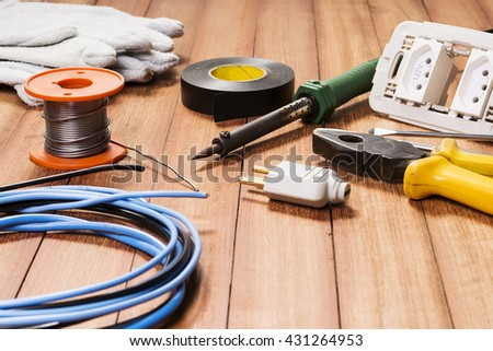Electrical equipment, tools, cables and accessories used by an electrician on a wooden surface. - stock photo