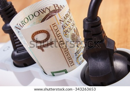 Electrical extension with connected plug and polish currency money on wooden floor, power board, concept of saving money on electricity, energy costs - stock photo