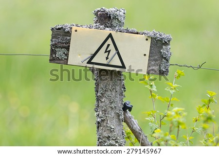 Electrical fence in old style with sign with the electric symbol - stock photo