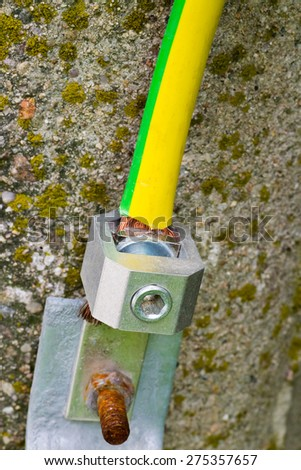 Electrical grounding of concrete pole with thick industrial  yellow cable macro - stock photo
