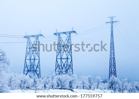 Electrical high-voltage metal pillars in winter - stock photo