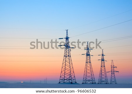Electrical mast morning snow sunrise voltage cables - stock photo