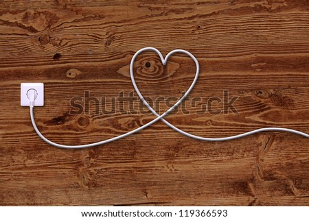 electrical outlet and wire in the shape of a heart - stock photo