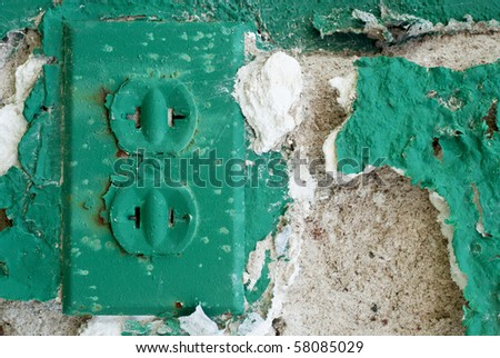 electrical outlet with green chipped paint in an old abandoned environment - stock photo