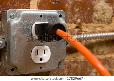 Electrical plug on a brick wall with a cord or extension cord plugged in, concept of connecting or power - stock photo