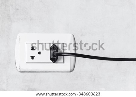 electrical plug on cement wall - stock photo