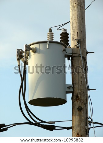 electrical power-line transformer on wooden pole - stock photo